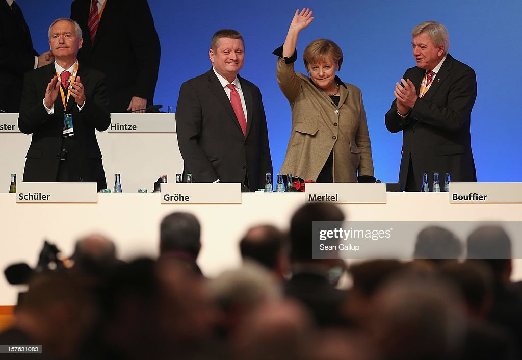 German Chancellor Angela Merkel, who is also chairwoman of the German Christian Democratic Union (CDU), waves to delegates as (from L to R) CDU Managing Director Klaus Schueler, CDU General Secretary Hermann Groehe and Hesse Governor Volker Bouffier look on at the conclusion of the CDU federal party convention on December 5, 2012 in Hanover, Germany. The CDU has a strong lead over its opponents though has recently lost the mayoral posts in several major German cities to opposition parties. Germany faces federal elections in 2013.