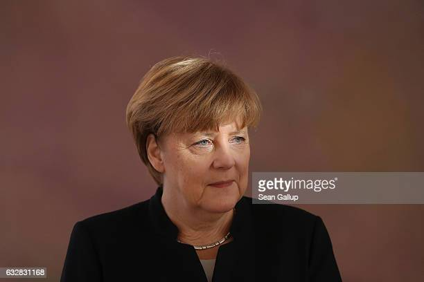German Chancellor Angela Merkel whose eyes are illuminated by sunlight attends a ceremony in which President Joachim Gauck appointed Sigmar Gabriel...