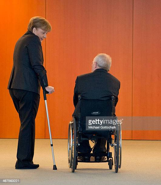 German Chancellor Angela Merkel with her crutches and German Finance Minister Wolfgang Schaeuble in his wheelchair talk to each other on the edge of...