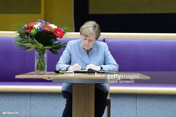 German Chancellor Angela Merkel writes a message in a book of condolence at the British embassy in Berlin on May 24 following the terror attack at...
