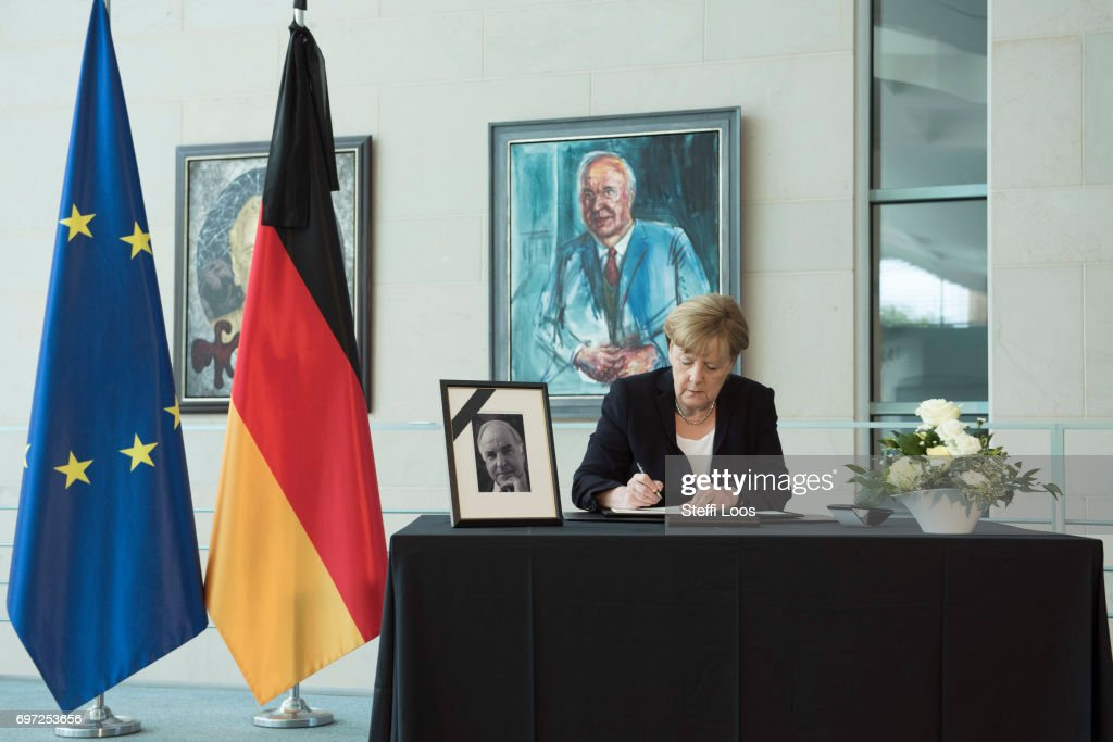 German Chancellor Angela Merkel writes in a book of condolence for former German Chancellor Helmut Kohl in front of the Chancellor's gallery at the Chancellery on June 18, 2017 in Berlin, Germany. Kohl, who was chancellor of Germany for 16 years and led the country from the Cold War through to reunification, died on June 16 at the age of 87.