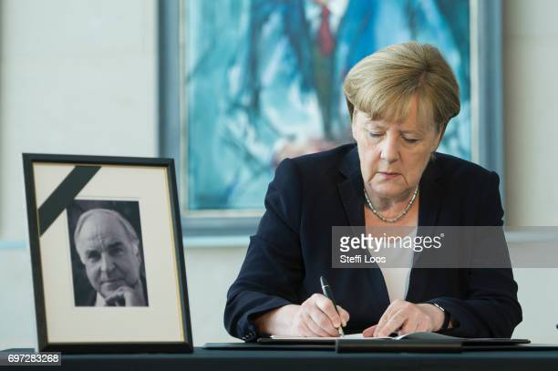 German Chancellor Angela Merkel writes in a condolences book for former chancellor Helmut Kohl in front of chancellor gallery at chancellery on June...