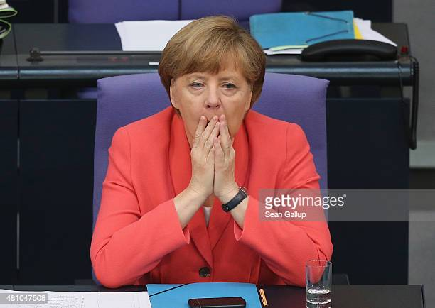 German Chancellor Angela Merkel yawns as she attends debates prior to a vote over the third EU financial aid package to Greece at an extraordinary...