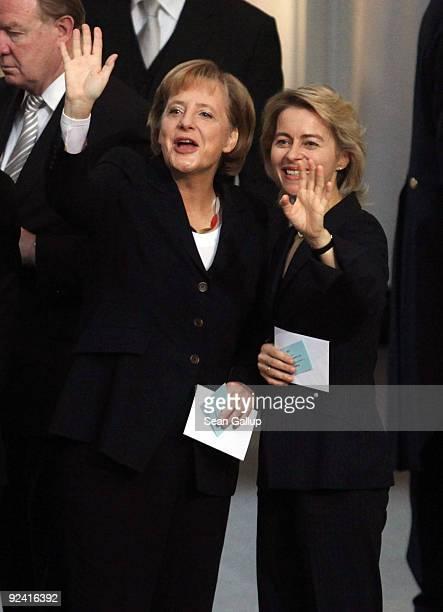 German Chancellor designate Angela Merkel and German Family Minister designate Ursula von der Leyen wave to von der Leyen's children while holding...