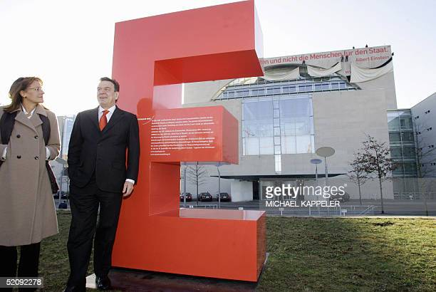 German Chancellor Gerhard Schroeder and Education Minister Edelgard Bulmahn stand in front of a giant E as workers in the background unveil banners...