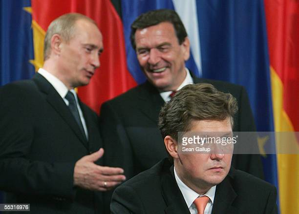 German Chancellor Gerhard Schroeder and Russian President Vladimir Putin talk shortly before Gazprom Chairman Alexei Miller signed an accord on the...
