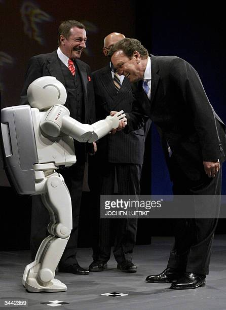 German Chancellor Gerhard Schroeder shakes hands with Honda's ASIMO robot during the opening of the Hanover trade fair 18 April 2004 as President of...