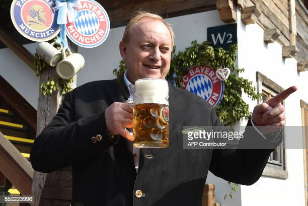 German chef author and businessman Alfons Schuhbeck holds a beer mug as he poses during the traditional visit of members of German first division...