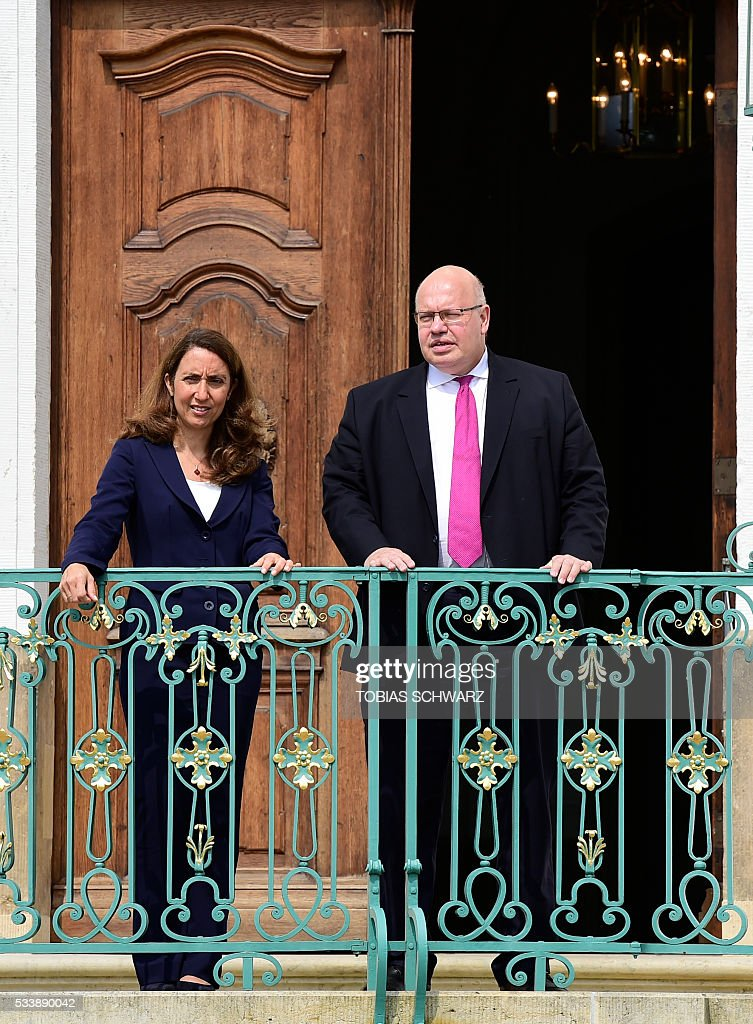 German Chief of Staff Peter Altmaier (R) and German Minister of State for Immigration, Refugees and Integration Aydan Ozoguz gesture as they arrive for the German government convention at meseberg Palace on May 24, 2016 in Meseberg. / AFP / TOBIAS