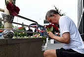 German citizen Thomas Tirolf knees as he brings flowers commemorating victims on the street near the shopping mall Olympia Einkaufzentrum OEZ in...