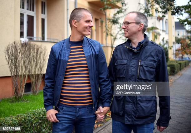 German couple Michael and Kai Korok pose on October 10 2017 in Berlin after they became the first samesex couple to adopt a child in Germany only ten...
