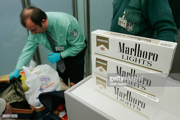 German customs officials confiscate undeclared cartons of cigarettes from a passenger arriving on a flight from Istanbul January 10 2006 in Berlin...