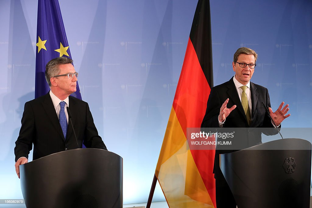 German Defence Minister Thomas de Maiziere and Foreign Minister Guido Westerwelle (R) addresses a press conference at the foreign ministry in Berlin on November 14, 2012. Germany revealed details of its likely drawdown plan for Afghanistan with the aim of seeing its number of troops fall to 3,300 by February 2014, the two ministers said. AFP PHOTO / WOLFGANG KUMM GERMANY OUT