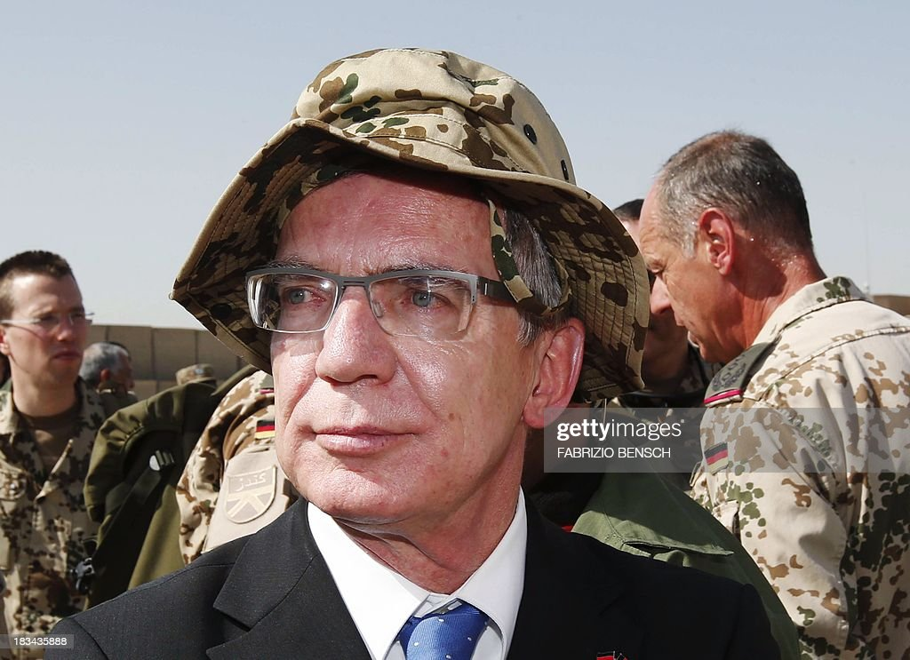 German Defence Minister Thomas de Maiziere arrives for the handover ceremony of a German base to the Afghan armed forces in Kunduz October 6, 2013. Soldiers of the German contingency of the International Security Assistance Force (ISAF) withdrew from their base in Kunduz and the camp will be used by the Afghan National Army (ANA) and the Afghan National Civil Order Police (ANCOP). AFP PHOTO / POOL / FABRIZIO BENSCH
