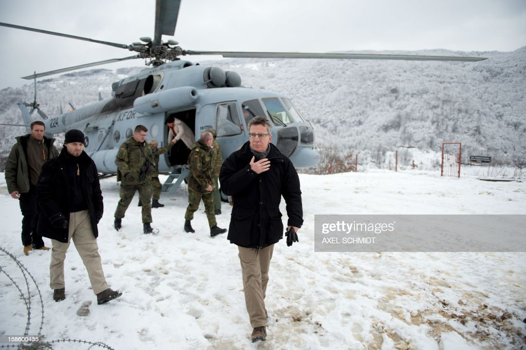 German Defence Minister Thomas de Maiziere (R) disembarks from a helicopter at the border post Dog 21 near Mitrovica in Kosovo where he visited German troops on December 20, 2012.
