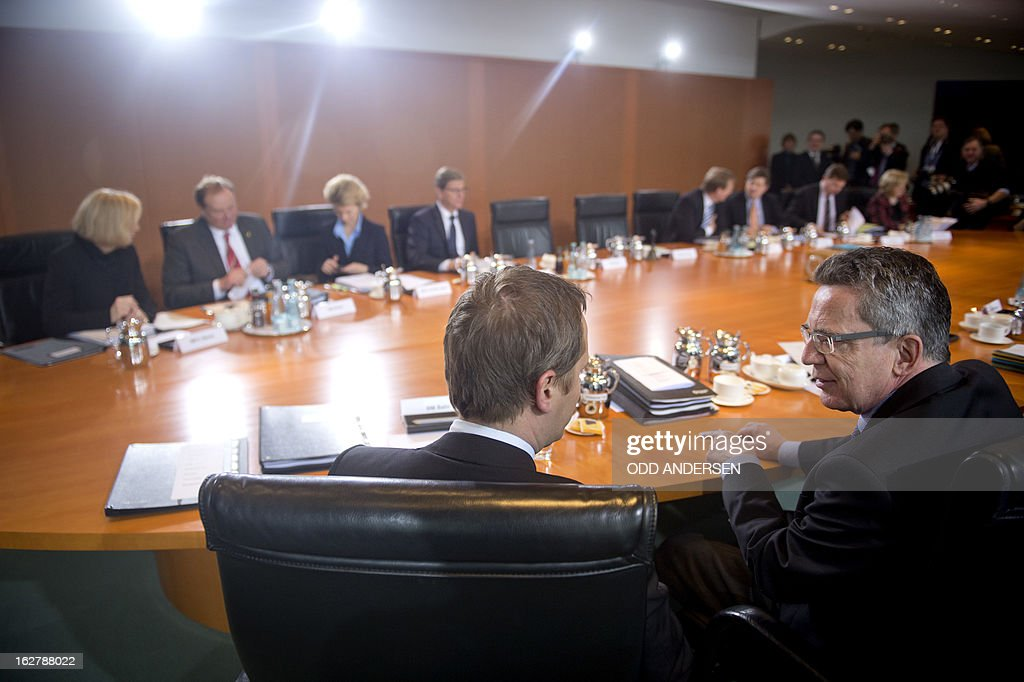 German defence minister Thomas de Maiziere (R) speaks with health minister Daniel Bahr (C) during the weekly cabinet meeting at the Chancellery in Berlin on February 27, 2013.