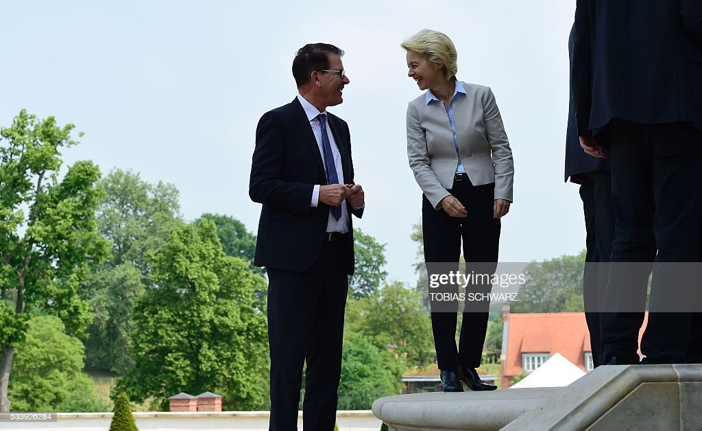 German Defence Minister Ursula von der Leyen and German Development Minister Gerd Mueller share a smile as they arrive for a closed meeting of the German cabinet at Meseberg Palace on May 24, 2016 in Meseberg, northeastern Germany. / AFP / TOBIAS