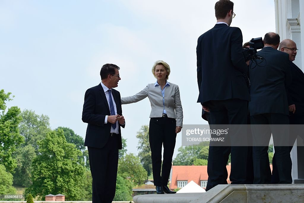 German Defence Minister Ursula von der Leyen (C) and German Development Minister Gerd Mueller (L) arrive for a closed meeting of the German cabinet at Meseberg Palace on May 24, 2016 in Meseberg, northeastern Germany. / AFP / TOBIAS
