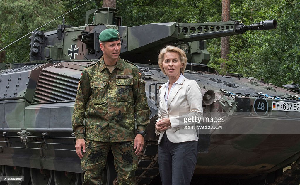 German Defence Minister Ursula von der Leyen (R) and Major Thorsten Nagelschmidt, commander of the 33rd Panzergrenadier bataillon pose in front of a new Puma Armoured Infantry Fighting Vehicle at their headquarters in Neustadt am Ruebenberge on June 29, 2016, prior to a drill. / AFP / JOHN