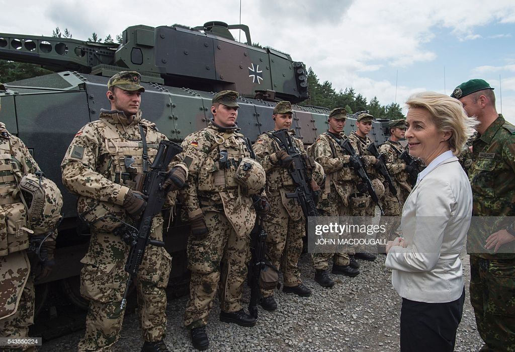 German Defence Minister Ursula von der Leyen (R) congratulates soldiers of the 33rd Panzergrenadier bataillon following a drill which involved the new Puma Armoured Infantry Fighting Vehicle (background), at their headquarters in Neustadt am Ruebenberge on June 29, 2016. / AFP / JOHN