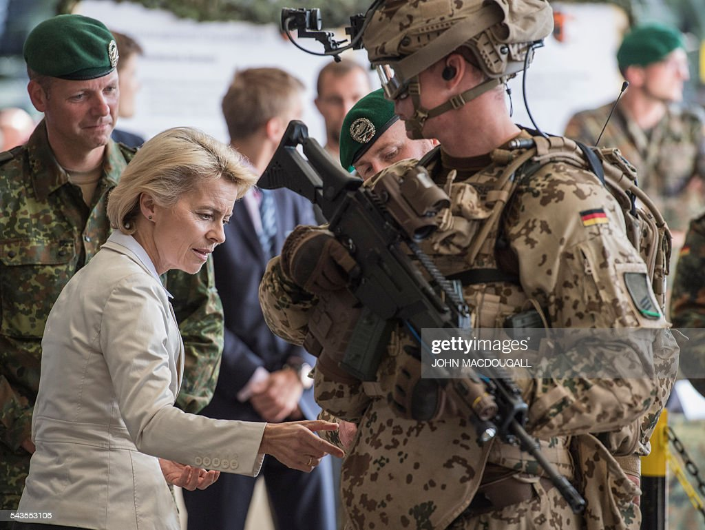 German Defence Minister Ursula von der Leyen inspects the kit of a soldier with the 33rd Panzergrenadier bataillon following a drill which involved the new Puma Armoured Infantry Fighting Vehicle at their headquarters in Neustadt am Ruebenberge on June 29, 2016. / AFP / JOHN