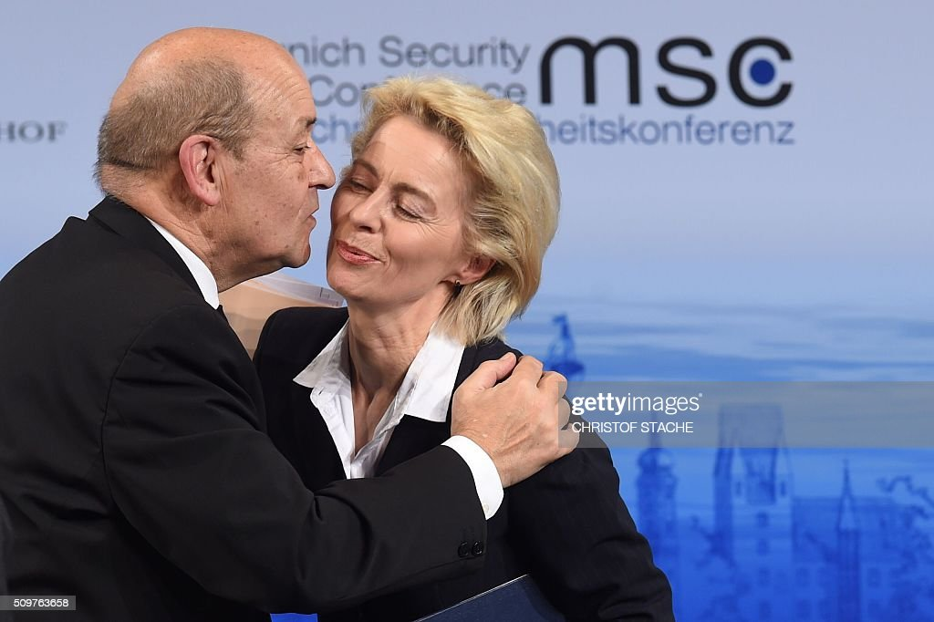 German Defence Minister Ursula von der Leyen is hugged by her French counterpart Jean-Yves Le Drian during the 52nd Munich Security Conference (MSC) in Munich, southern Germany, on February 12, 2016. The Munich Security Conference takes place here until February 14, 2016. / AFP / Christof Stache