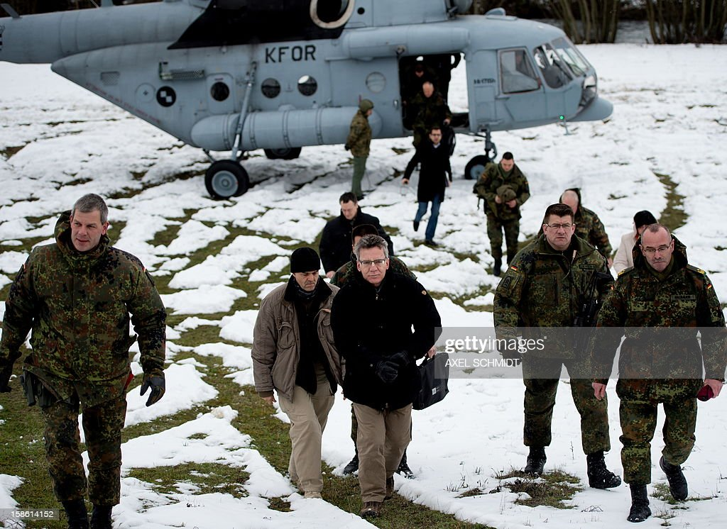 German Defende minister Lothar de Maiziere disembarks from a helicopter of the KFOR (Kosovo Force) in Zupce, Kosovo, where he visited German troops on December 20, 2012.