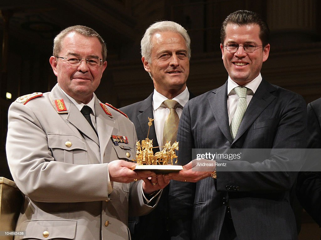 German Defense Minister <a gi-track='captionPersonalityLinkClicked' href=/galleries/search?phrase=Karl-Theodor+zu+Guttenberg&family=editorial&specificpeople=5585450 ng-click='$event.stopPropagation()'>Karl-Theodor zu Guttenberg</a> (R) and Guenter Weiler (L), general inspector of the German army (Bundeswehr) hold up the award as Peter Ramsauer (C), Germany's minister of transport, buildings and urban affairs look on during the Quadriga awards ceremony at the Konzerthaus on Gendarmenmarkt on October 3, 2010 in Berlin, Germany.
