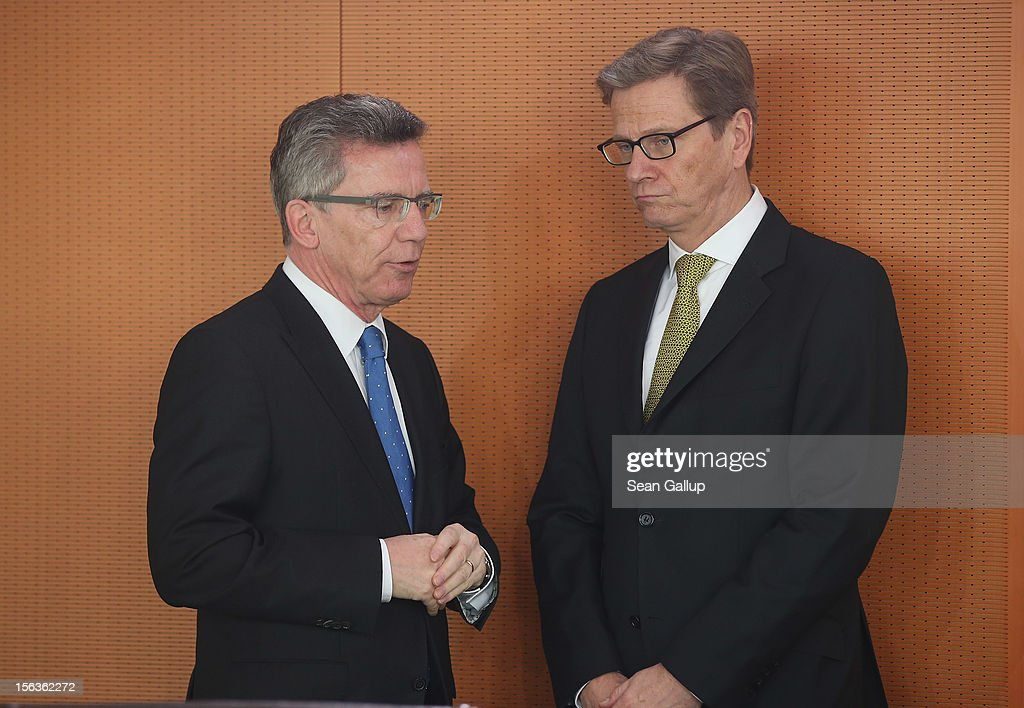 German Defense Minister Thomas de Maiziere (L) and Foreign Minister Guido Westerwelle chat upon their arrival at the German government weekly cabinet meeting on November 14, 2012 in Berlin, Germany. High on the morning's agenda is the annual weapons export report (Ruestungsexportbericht 2011).