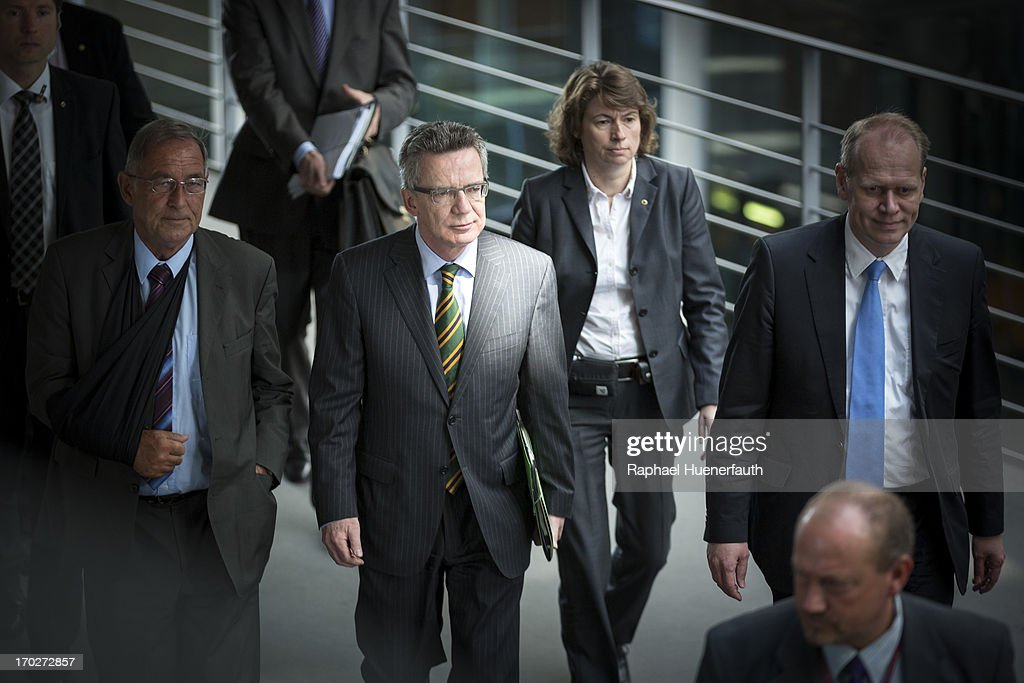 German Defense Minister Thomas de Maiziere (C) and his speaker Stefan Paris (R) arrives to answer questions from parliamentarians at the Bundestag defense commission on June 10, 2013 in Berlin, Germany. De Maiziere is under increasing pressure following the 'EuroHawk' drone debacle, in which de Maiziere announced recently that the German government would cancel the military project, which has already consumed EUR 562 million, due to the complications with domestic flight certification. The 'EuroHawk' is a modified version of the Northrop Grumman RQ-4 Global Hawk.