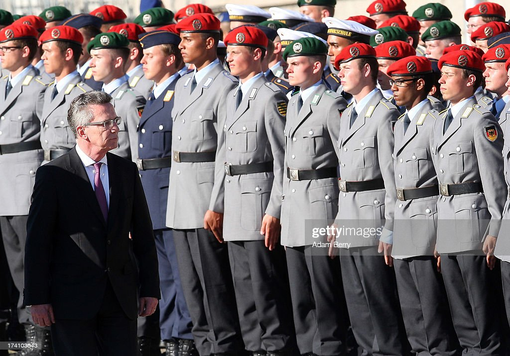 German Defense Minister Thomas de Maiziere (L) reviews new German Bundeswehr soldiers during a swearing-in ceremony for new recruits of the Bundeswehr, the armed forces of the Federal Republic of Germany, in front of the Reichstag building on July 20, 2013 in Berlin, Germany. In the annual ceremony, new soldiers take office on the anniversary of the assassination attempt on Adolf Hitler by Claus Schenk Graf von Stauffenberg.