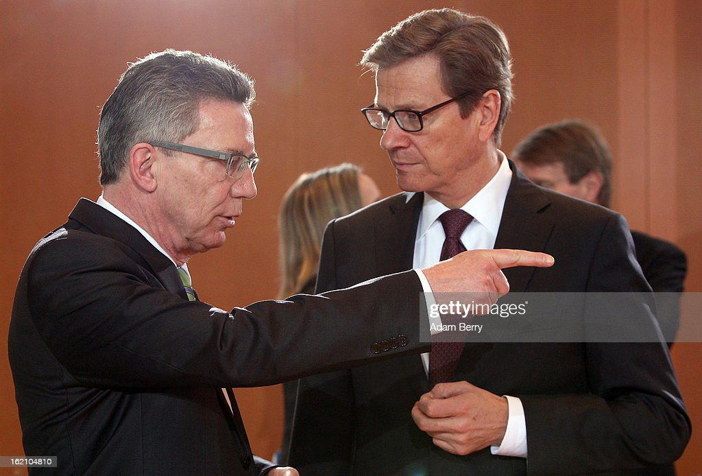 German Defense Minister <a gi-track='captionPersonalityLinkClicked' href=/galleries/search?phrase=Thomas+de+Maiziere&family=editorial&specificpeople=618845 ng-click='$event.stopPropagation()'>Thomas de Maiziere</a> (L) speaks to German Foreign Minister <a gi-track='captionPersonalityLinkClicked' href=/galleries/search?phrase=Guido+Westerwelle&family=editorial&specificpeople=208748 ng-click='$event.stopPropagation()'>Guido Westerwelle</a> as they arrive for the German federal cabinet meeting on February 19, 2013 in Berlin, Germany. High on the cabinet meeting agenda will be Germany's military role in Mali, for which the country has already promised logistical support based on the situation on the ground to help an initial battle against Islamic insurgents. Germany has also pledged two C-160 transport planes as well as backing an EU plan to send 200 military advisers to the African nation.