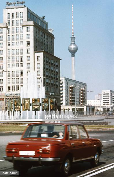 German Democratic Republic Bezirk Berlin East Berlin red Wartburg car at the square Strausberger Platz in front of the building Haus des Kindes and...