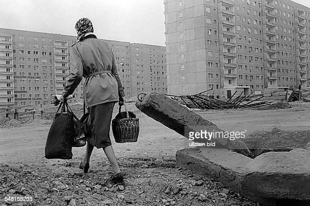 German Democratic Republic Bezirk KarlMarxStadt KarlMarxStadt woman is carrying her shopping bags walking through construction waste of the new build...