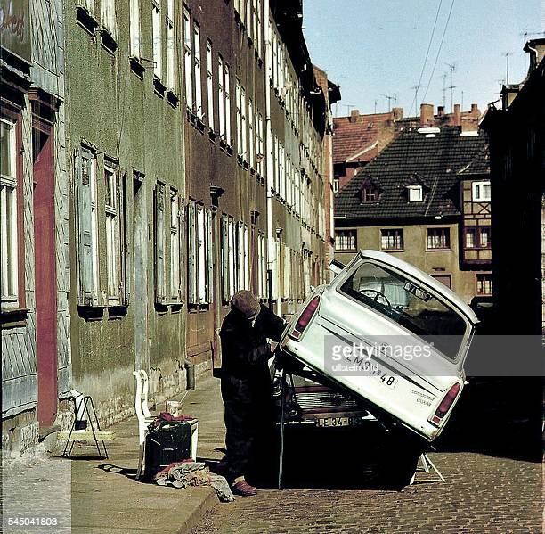 German Democratic Republic Erfurt man repairing his Trabant on the street date unknown about 1980