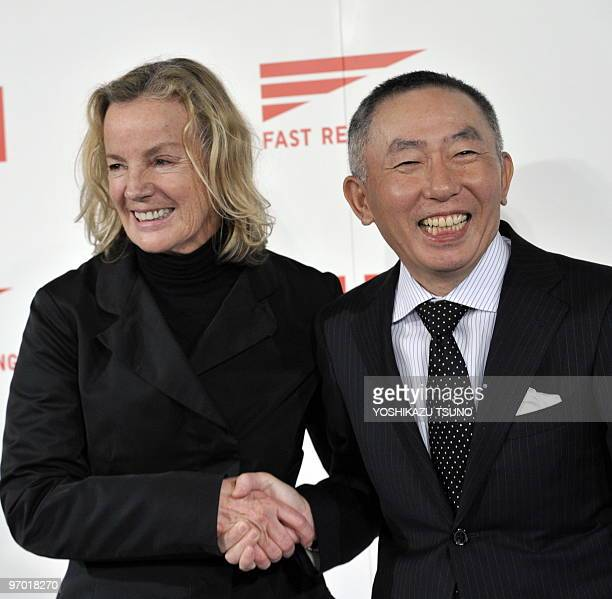 German designer Jil Sander shakes hands with Japan's casual apparel giant Fast Retailing known as Uniqlo brand president tadashi Yanai as they...