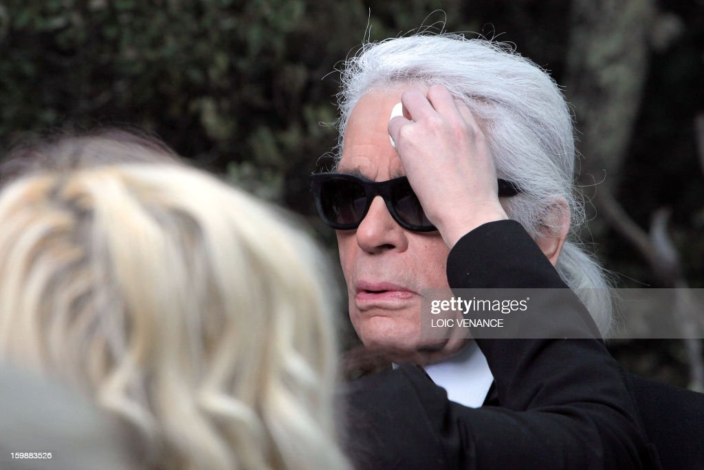 German designer Karl Lagerfeld has some make-up applied at the end of his Chanel Haute Couture Spring-Summer 2013 collection show on January 22, 2013 at the Grand Palais in Paris. AFP PHOTO / LOIC VENANCE