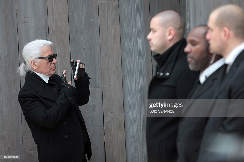 German designer Karl Lagerfeld takes photos at the end of his Chanel Haute Couture Spring-Summer 2013 collection show on January 22, 2013 at the Grand Palais in Paris. AFP PHOTO / LOIC VENANCE