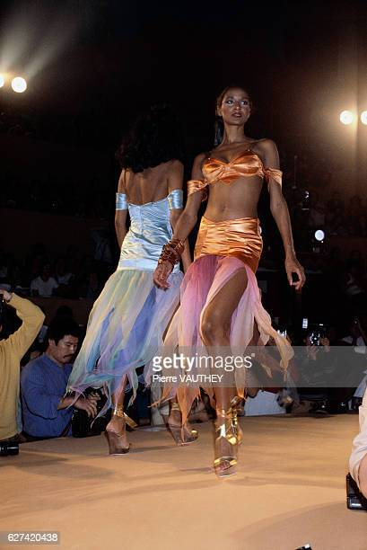 German designer Thierry Mugler shows his 1980 springsummer women's readytowear collection in Paris The model is wearing a satin bandeau top paired...
