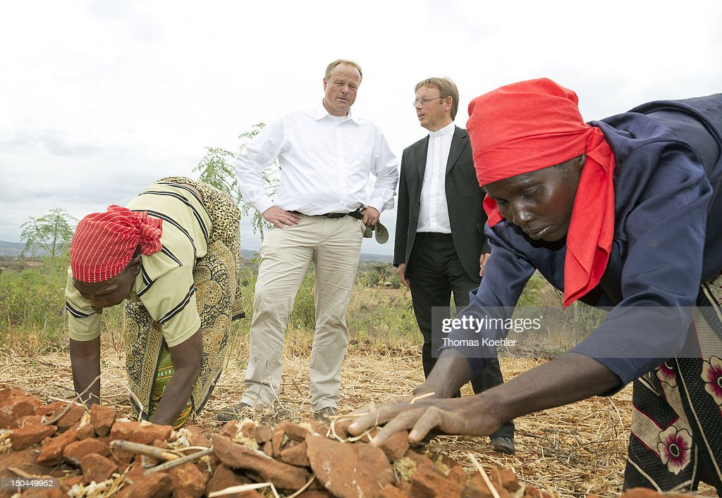 German Development Minister Dirk Niebel (C) and German Prelat Karl Juesten (C,R) visit a small farm on August 18, 2012, Ishiara in Kenya. The people who live at the farm are supported by the German church development organization Misereror. Niebel was in Kenya on an official visit to discuss trilateral projects with Israel and Kenya.