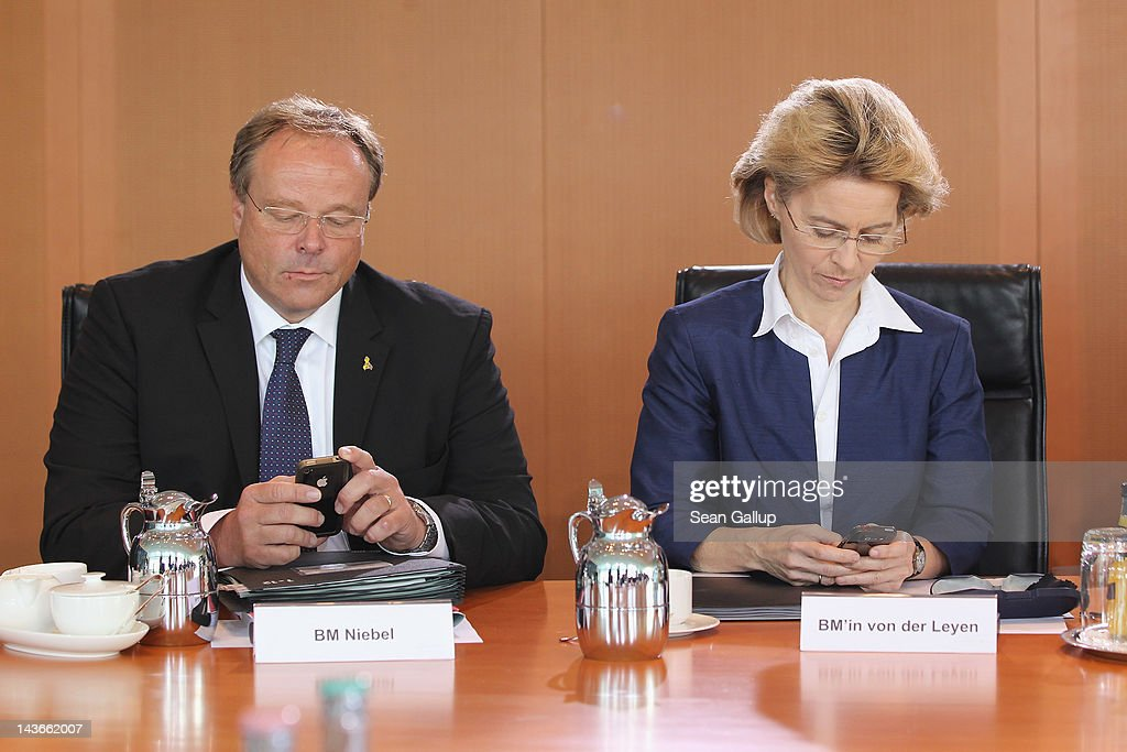 German Development Minister Dirk Niebel and Minister of Work and Social Issues Ursula von der Leyentype text message on their mobile phones upon their arrival at the weekly cabinet meeting on May 2, 2012 in Berlin, Germany. Among topics on the morning's agenda was a the creation of a government supervisory body to oversee prices gasoline retailers charge motorists at petrol staitons.