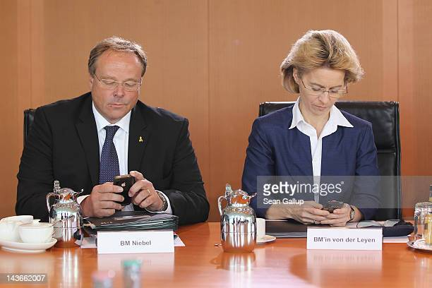 German Development Minister Dirk Niebel and Minister of Work and Social Issues Ursula von der Leyentype text message on their mobile phones upon...