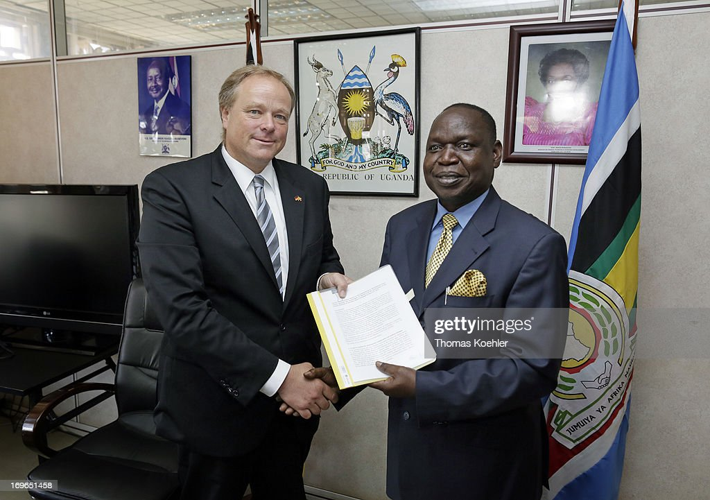 German Development Minister <a gi-track='captionPersonalityLinkClicked' href=/galleries/search?phrase=Dirk+Niebel&family=editorial&specificpeople=710721 ng-click='$event.stopPropagation()'>Dirk Niebel</a> (L) and Ugandan Minister of State for Finance Fred Omach (R) show the minutes of the government negotiations on May 30, 2013 in Kampala, Uganda.