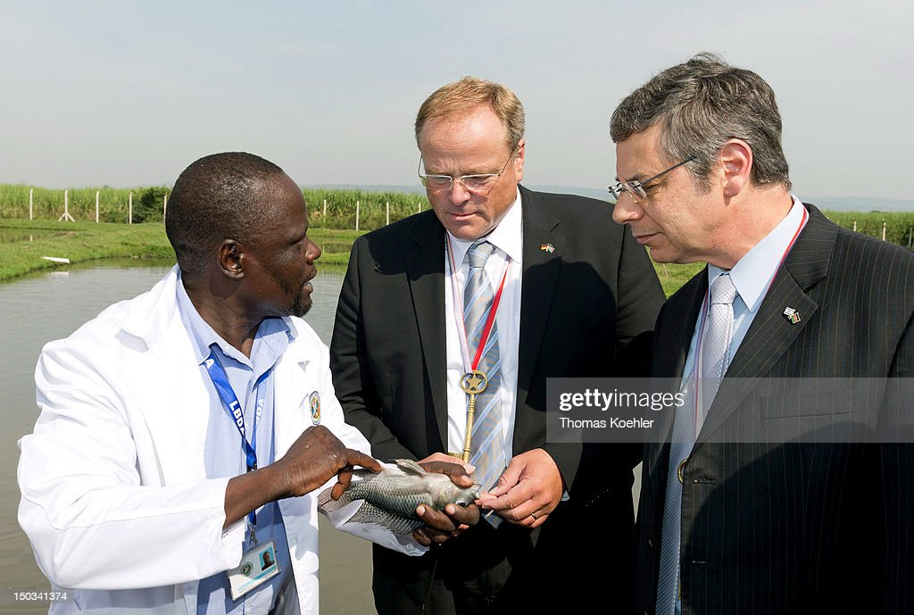 German Development Minister Dirk Niebel (M) and Vice Foreign Minister of Israel, Danny Ayalon (L), visit a fish farm on August 16, 2012, in Kisumu, Kenya. Niebel was in Kenya on an official visit to discuss trilateral projects with Israel and Kenya.