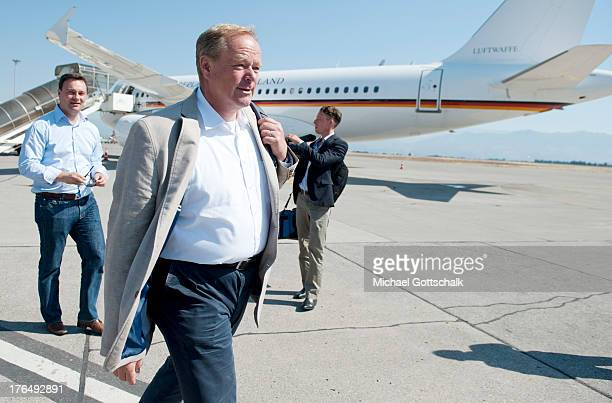 German Development Minister Dirk Niebel goes on a airfield in front of a plane of air service of German government on August 7 2013 in Podgorica...