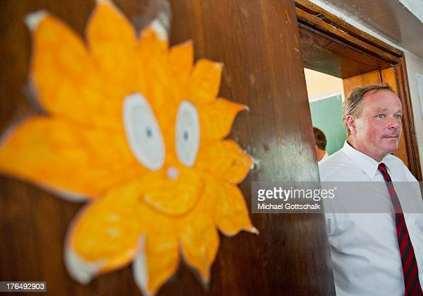 German Development Minister Dirk Niebel passes a picture of a sunflower during his visit of Maksim Gorki School on August 8 2013 in Podgorica...