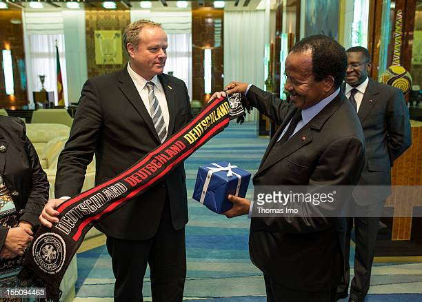 German Development Minister Dirk Niebel presents a DFB football scarf as a gift to the President of Cameroon Paul Biya on October 29 2012 in Yaounde...