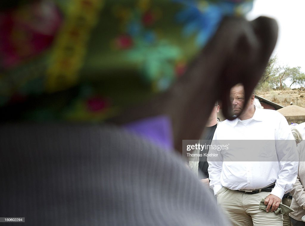 German Development Minister Dirk Niebel (M, seen through the ear of an inhabitant) visits a small farm on August 18, 2012, in Ishiara, Kenya. The people who live at the farm are supported by the German church development organization Misereror.
