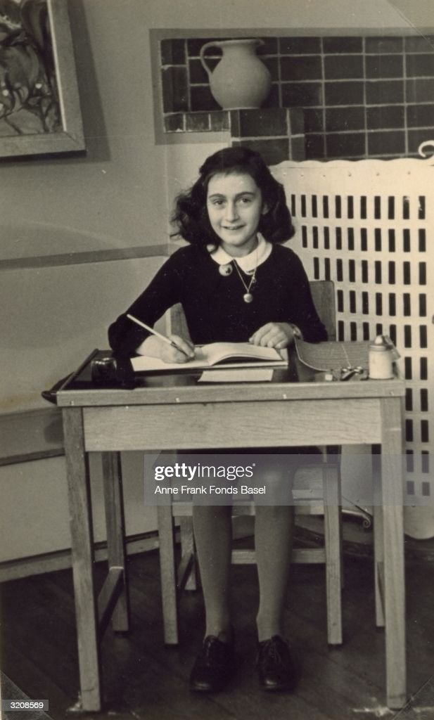 German diarist and Holocaust victim <a gi-track='captionPersonalityLinkClicked' href=/galleries/search?phrase=Anne+Frank&family=editorial&specificpeople=173492 ng-click='$event.stopPropagation()'>Anne Frank</a> (1929 - 1945) sits at a wooden desk, writing in a journal, 1940.
