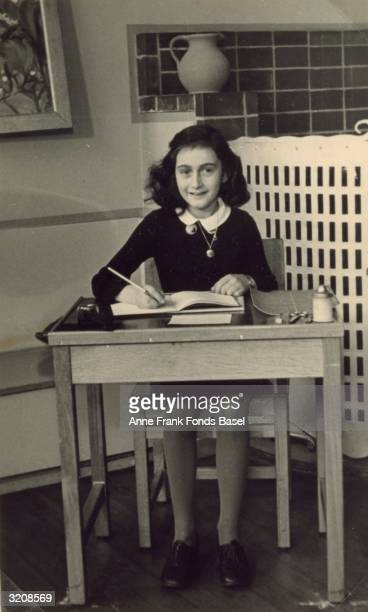 German diarist and Holocaust victim Anne Frank sits at a wooden desk writing in a journal 1940